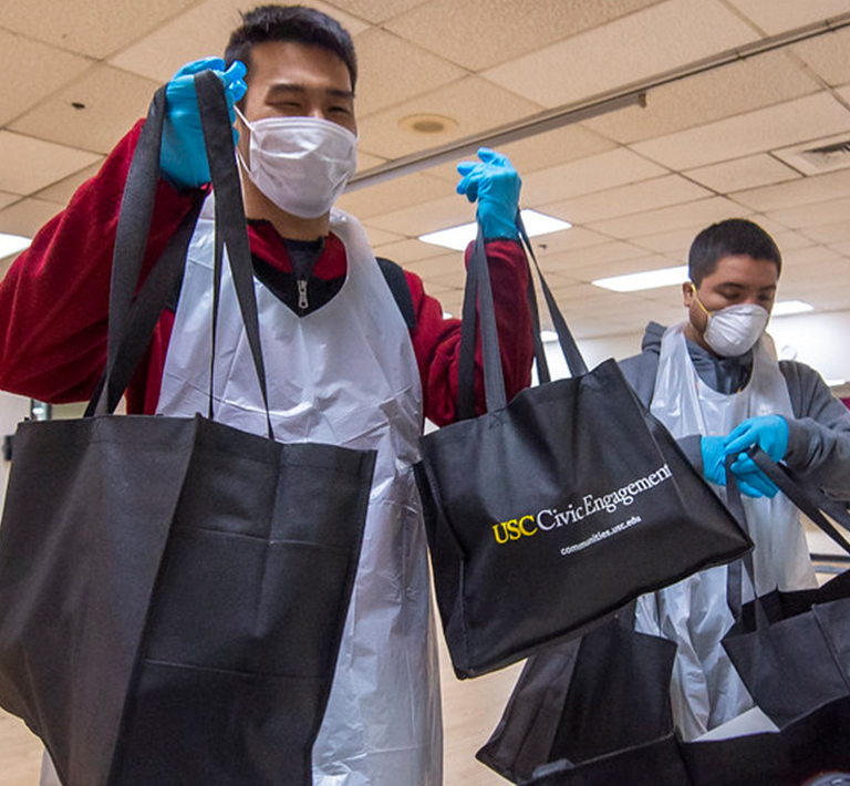 Volunteers in masks handing out supplies in a USC Civic Engagement bag
