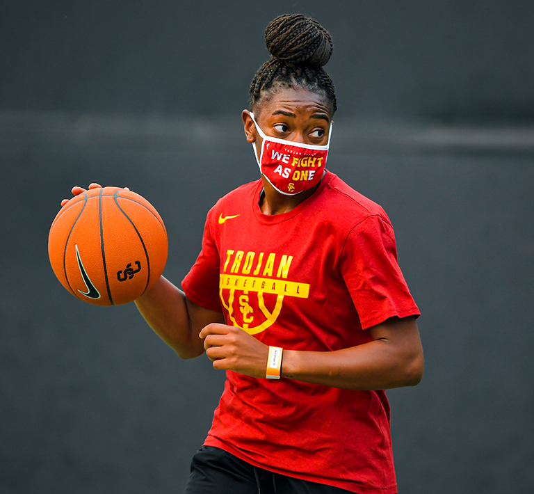 USC women's basketball player wearing a mask and dribbling a ball.
