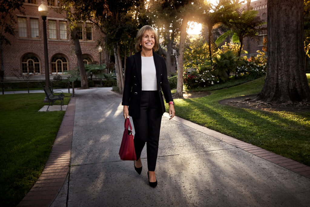 President Folt walking on one of USC's campus paths.