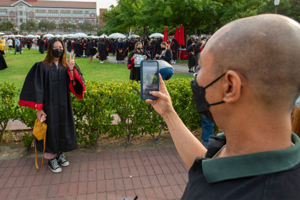 A family member taking a picture of a USC student during convocation