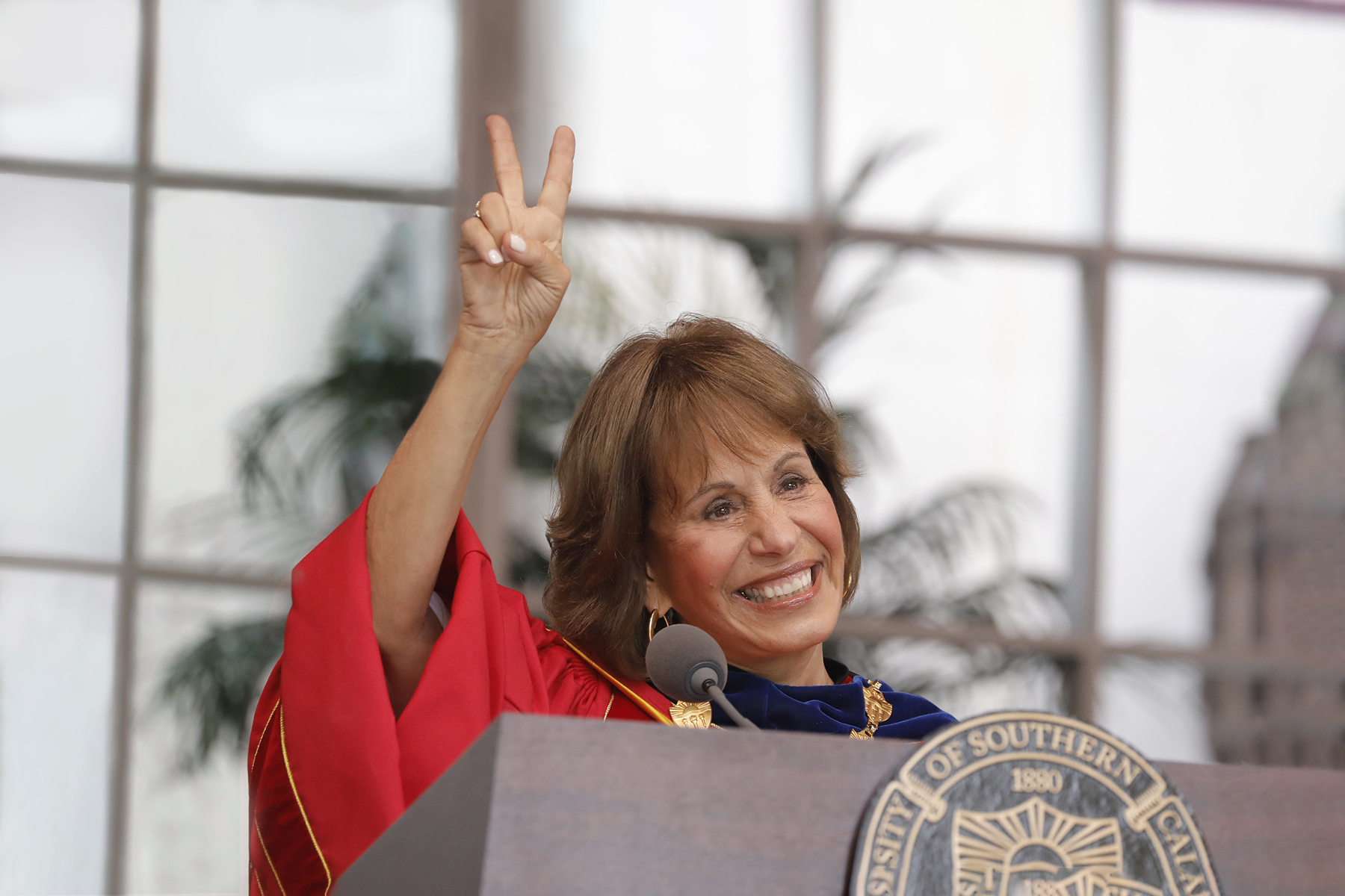Carol Folt shows the victory sign to the crowd during commencement